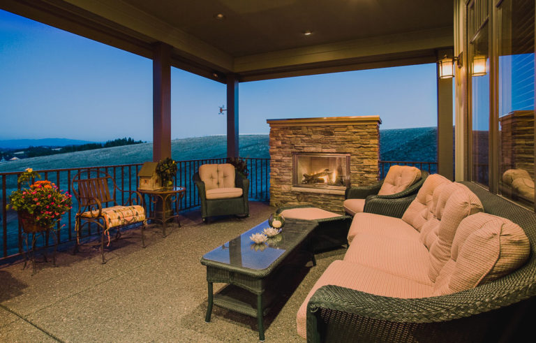 covered patio, iron railing, exposed aggregate concrete, outdoor fireplace
