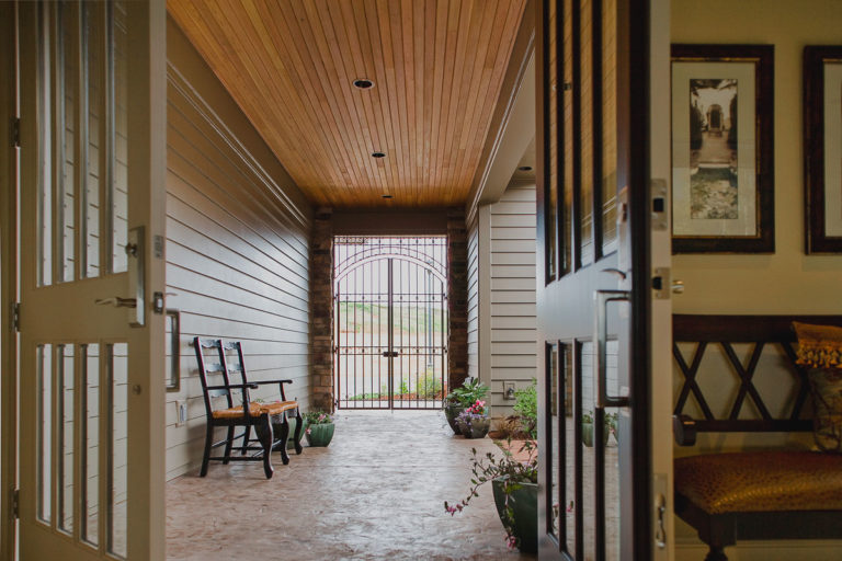 stamped concrete, iron gate, cedar ceiling, artisan hardi plank siding, entry door